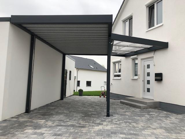 Carport bündig mit Garage und schräg laufender Eingangsüberdachung aus Polycarbonat